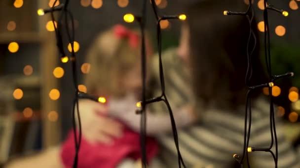 Porträt der glückliche Mutter und entzückende Baby hinter gelben Girlanden in den Raum mit grünen Fichte Zweigen geschmückt zu verwischen. Mama und niedlichen Babymädchen in schönen Zimmer, Familienfeier-Konzept