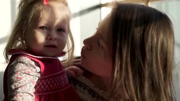 schöne kleine Mädchen mit niedlichen pausbäckigen Wangen lächelnd in den Armen ihrer Mutter und umarmte sie. schöne brünette Mutter küsst ihr Kind gegen das Fenster, während sie Zeit miteinander verbringt.