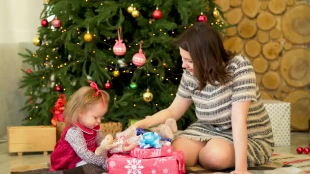 Happy mother with her little daughter playing near the Christmas tree. Beautiful mother playing with her little daughter sitting in a chair near the festive Christmas tree