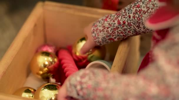 Little girl playing with toys to decorate the Christmas tree. A box of Christmas toys
