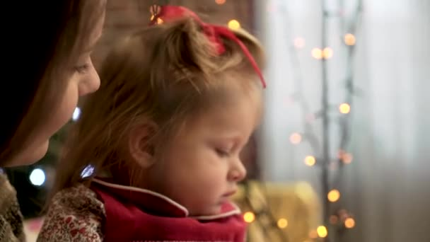 Frohe Weihnachten. Mutter und Kind Tochter mit einem glühenden Weihnachtsgirlande. Mutter und junge Tochter, die Girlande