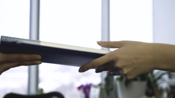 Woman reports to the Manager document folder. Close-up of female hands transmitting a folder of documents in the office. The concept of office work.
