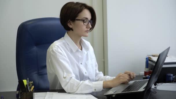 Fiatal üzletasszony működő-ra egy laptop, az irodában. Üzletasszony fáradt-ból működő-on-a laptop, ő veszi le a szemüvegét, és megtöröl őt fáradt szemek.
