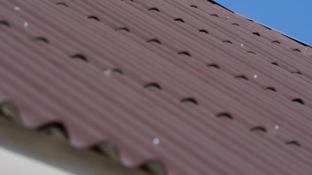 Střecha s šedou střešní tašky a jasně modré obloze nějaké mraky na slunečný den, střecha pozadí dlaždic, textury. Staveniště zastřešení černé dlaždice