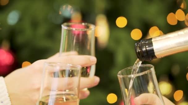 Celebrazione o partito. Persone che tengono i vetri di champagne che producono un pane tostato. Tintinnio di bicchieri di champagne nelle mani su sfondo di luci