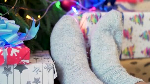 Bílé pletené ponožky na ženské nohy pozadí nazdobený vánoční stromeček. Svátků a nového roku koncept. Vyšívané pletené ponožky s vánoční strom v pozadí