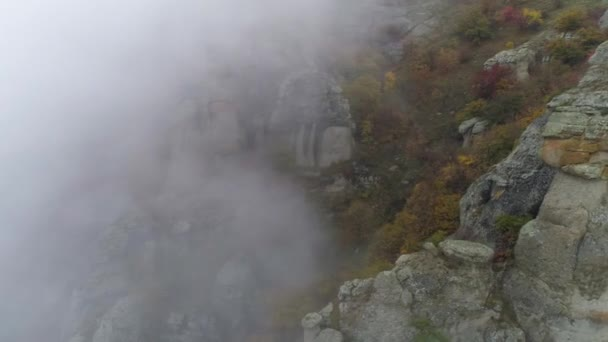 Majestical mountains in clouds with yellow, autumn trees. Shot. Landscape with beautiful high rocks and dramatic fog with yellow trees, nature background.