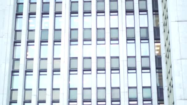 Multiple closed windows on a large, white blur office building, geometric background with lots of window rows. Many Windows on a high building, exterior.
