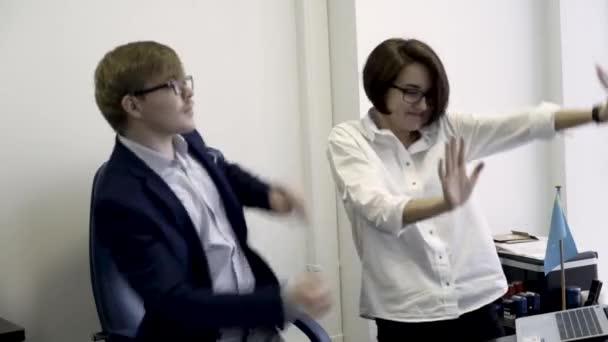 Mladí hosté kolegy muž v obleku a brýle a žena v bílé košili tančí v kanceláři na pozadí bílé zdi. Legrační mužských a ženských co pracovníků při práci se zbláznil