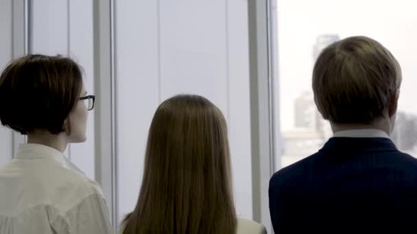 Pohled zezadu na obchodní skupiny stojí v řadě a dívat se skrz okno. Dvě ženy a muž co pracovníků stáli spolu v kanceláři poblíž velkých oken a při pohledu na město.