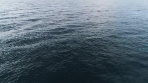 Pohled shora na modré moře vlnky. Střela. Pozadí vodní plochy s hladké vlny a vlnky. Pohyb z modré hladiny moře dává klid a radost