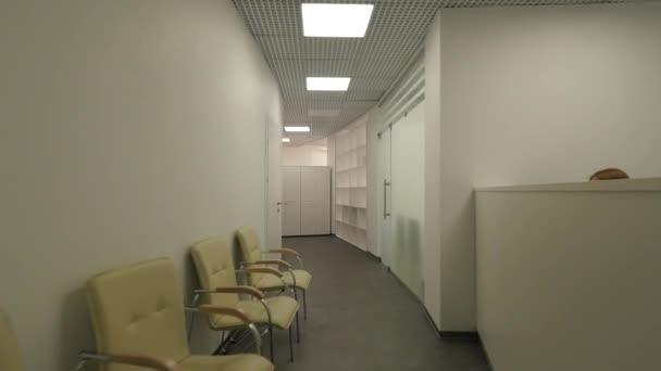Dlouhé, obloukovité kancelář haly a recepce. Koridor veřejné budovy s židlemi nedaleko zdi a mnoho dveří.