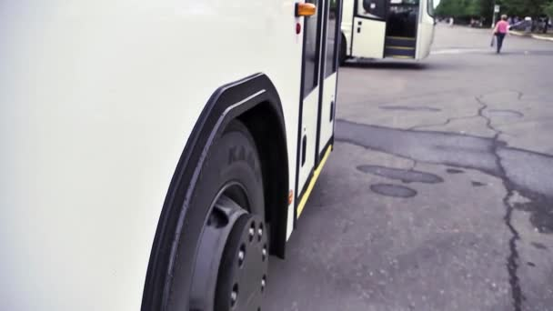 Side view of the white bus and bus wheel stopping on grey asphalt background. Scene. Close up of white passenger bus and its wheel, commercial transport wheels concept.