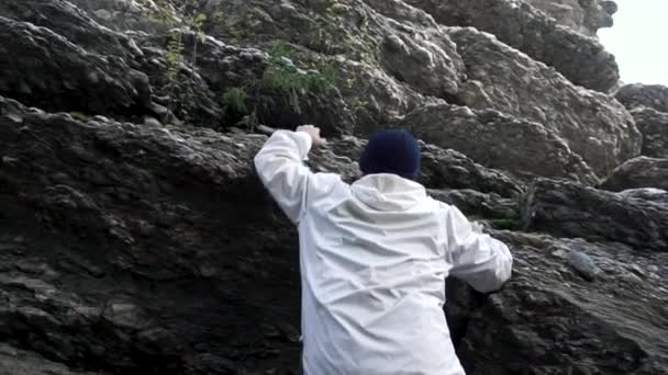 Hiker in white jacket climbing a mountain in the forest on bright sky background, bottom view. Footage. Rear view of a man climbing rocks in a sunny day, slow motion.