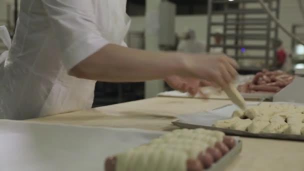Közelről csomagolva nyers leveles tészta, a pékség és guruló ki tésztát baker nő kolbász. Nyers hot dog hengerelt tésztát nő baker kezében, élelmiszer elkészítése koncepció.
