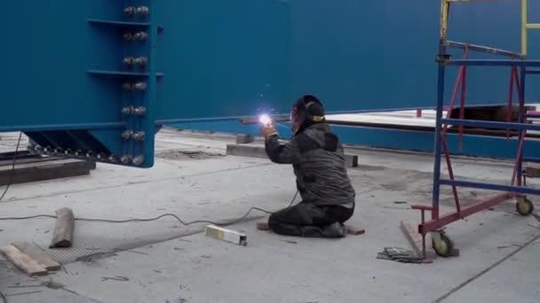 Obloukové svařování oceli ve staveniště. Klip. Muž v masce je navařen na staveništi