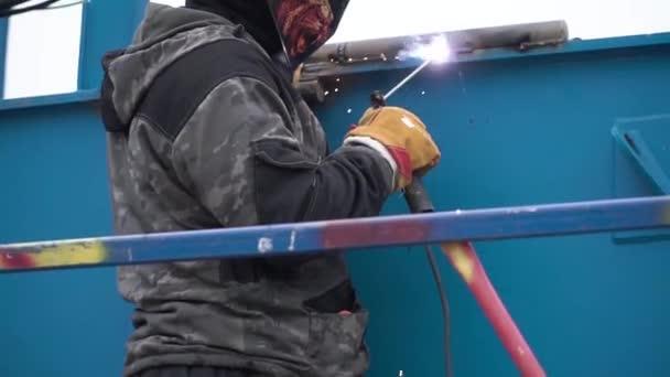 Obloukové svařování oceli ve staveniště. Klip. Muž v masce je navařen na staveništi.