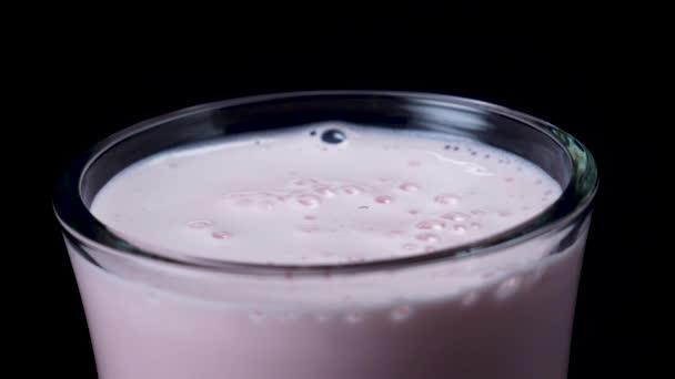 Detail ze skla s jahodový koktejl. Rám. Čerstvě šlehané růžový koktejl z čirého skla na černém pozadí izolované