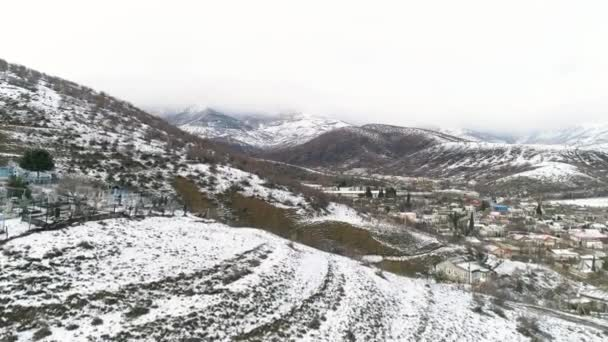 Winter landscape with snowy fields, trees, and village on cloudy sky background. Shot. Aerial for snowy mountain slopes, forest, and rare houses.