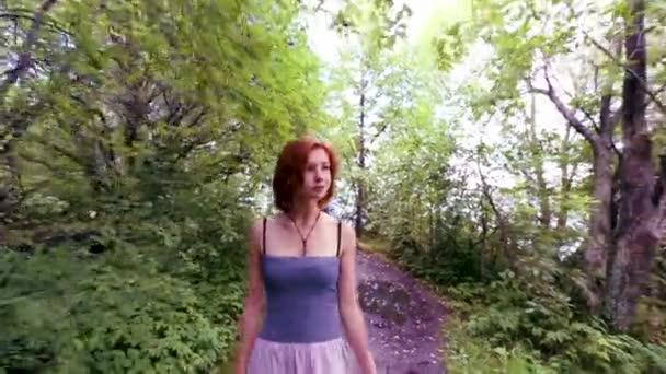 Gyönyörű, fiatal, vörös hajú nő séta zöld erdőben, egy napsütéses napon. Elég világos hajú lány séta erdőben az úton, és nézett körül.