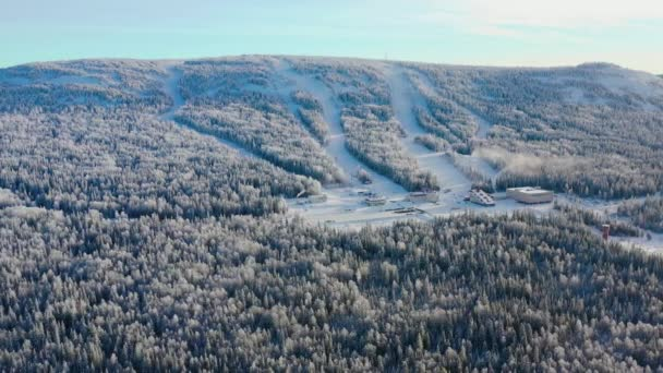 Top view of ski base with slopes on mountain. Footage. Panorama of snow-covered mountains with ski slopes and recreation among coniferous forest on clear winter day.