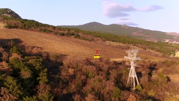 Anténa pro žluté lanová dráha s pohyblivými na pozadí svahu stromy. Střela. Lanová dráha pohybu nad zalesněnými kopci sjezdovka v západu slunce.