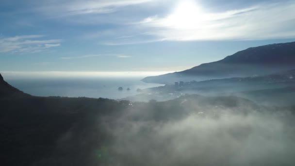Letecký pohled na nekonečném oceánu, pobřeží nedaleko vysoké hory v mracích. Střela. Ohromující pohled na skály ve stínu slunce, modrý oceán, malé město dolů v údolí na zamračená obloha pozadí