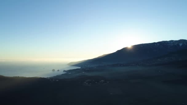 Ranní východ slunce nad horami v blízkosti moře na pozadí modré oblohy, krásy přírody. Střela. Malebné východ slunce na pobřeží moře, údolí a vysoké skále