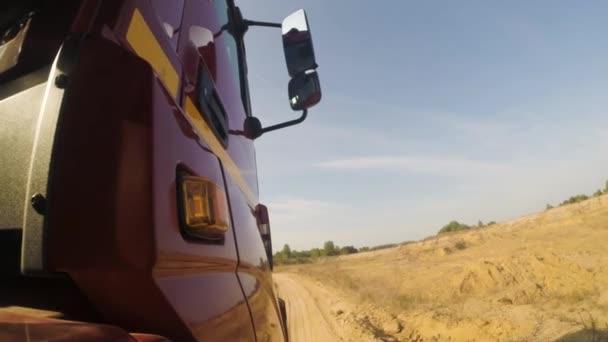 Boční pohled červený tahač na prašné nezpevněné venkovské silnici podél zelené stromy před sebou. Scénu. Obrovské nákladní automobil na zemi, prašné cestě na zamračená obloha pozadí, pohled z kola