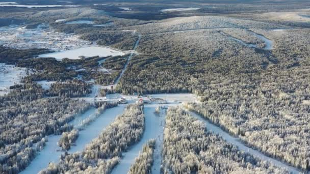 Aerial view of cable car cabins and ski resort surrounded by forest in winter. Footage. Outdoor sports