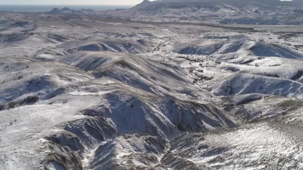 Aerial view in mountain ranges and hills covered by snow near the sea. Shot. Wonderful landscape