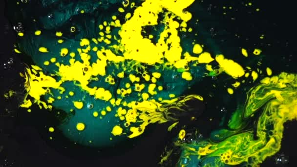 Close-up of yellow and blue paint stains mixing with dark surface. Color creation and art concept.