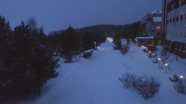 Cesta záchrany večer v zimě. Klip. Pohled shora středisek temný večer cesty v oblačné počasí. Klid v parku cestě v sněžení