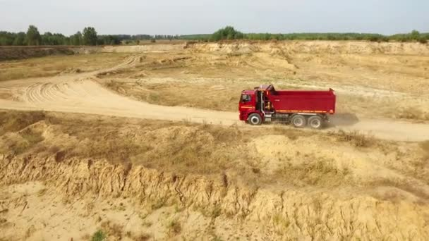 Aerial view the red truck moving on sand track against grey sky and trees on the background. Beautiful view from above.