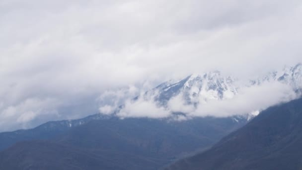 Beautiful mountain landscape with snowy peaks and low clouds. Cloudy low sky overhanging snowy peaks of wooded mountains. Top view of amazing cloud mountain landscape