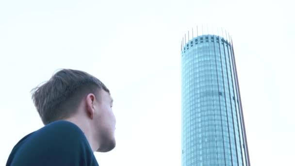 Detail mladík při pohledu na vysoký mrakodrap. Lidé a budovy, pohled zdola.