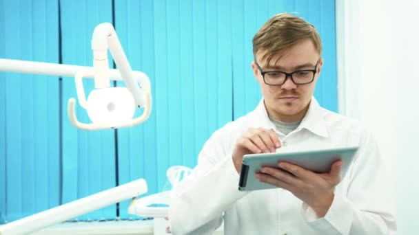 Close-up of young man dentist in white coat looking at his tablet in dental office. Dental care.