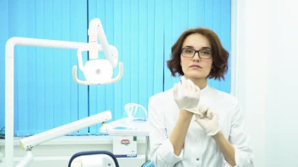 junge Ärztin mit Brille und weißem Mantel, die im Zahnarztkabinett weiße medizinische Handschuhe anzieht. eine strenge Zahnärztin zieht Handschuhe an, blickt in die Kamera und macht sich bereit.