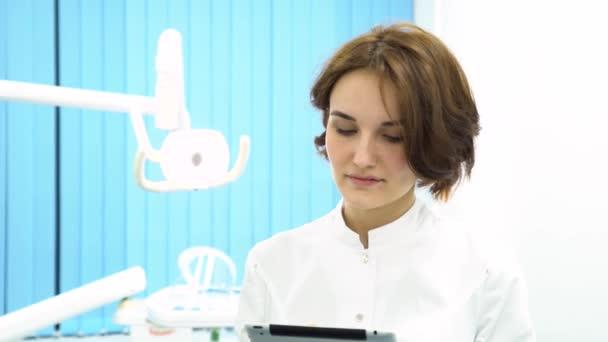 Lékařka s tablet pc počítač stojící v lékařské koncept kabinetu, zdravotní péče, technologie a medicíny. Zavřít za krásného ženského lékaře iin bílý plášť poklepáním na tabletu.