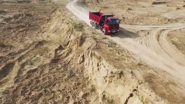 Detail velké a prázdné červené sklápěč pro písek dodávku na úzké písčité závodiště. Scénu. Pohled shora.