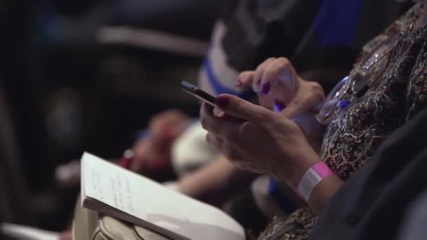 Mädchen mit Notepad sitzt im Konferenzraum und scrollt der Bildschirm. Lager. Nahaufnahme von weiblichen Händen sind Sms tippen, auf Smartphone. Nahaufnahme von weiblichen Händen scrollen etwas in das Smartphone