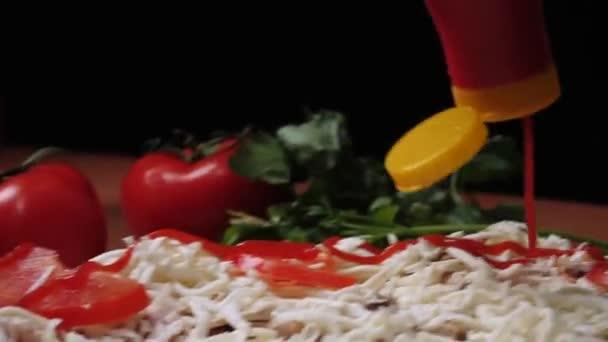 Nalévání kečupu na pizzu detail. Rám. Detail ruce šíření omáčka na pizzu