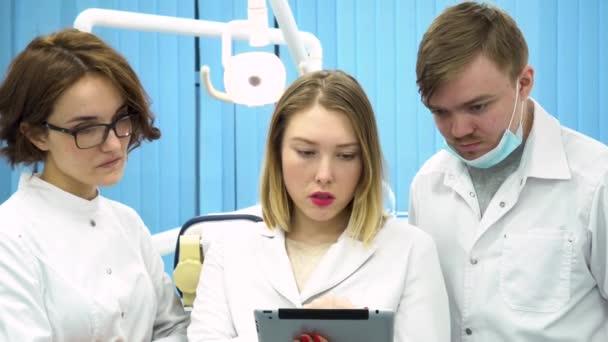Drei Zahnärzte betrachten eine Tablette in einem medizinischen Schrank und diskutieren Diagnose, Medikamentenkonzept. Mediziner schauen im Büro auf den Computer.