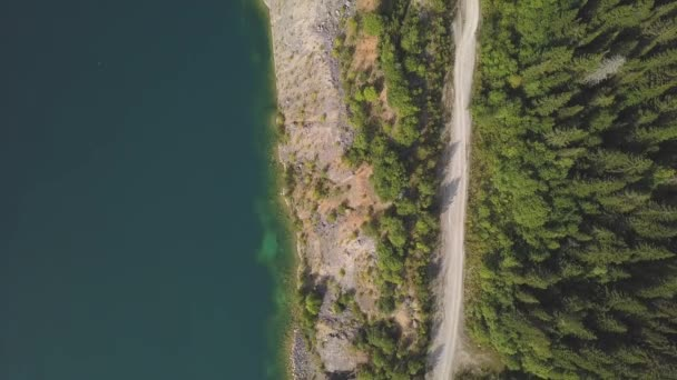Amazing aerial drone shot road along a lake. Clip. Pond and road in mountains top view