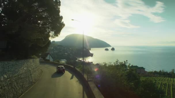 Amazing aerial view of beautiful Mediterranean landscape with curvy mountain road in the coastal seaside town at sunrise. Shot. City Bay and mountain road, beautiful aerial view