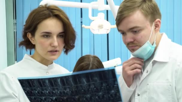 Dentists man and woman looking at full body x-ray radiographic image, ct scan, mri with a patient lying behind. Young doctors in lab coats discussing diagnosis in dental clinic office.