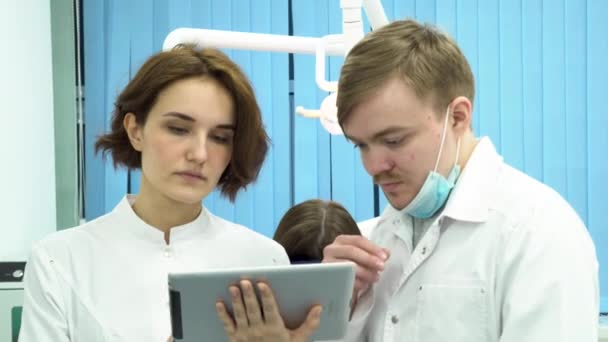 Serious doctors working together with tablet in the dental care cabinet with a patient lying behind. Dentists male and female discussing test reports that is shown on their tablet computer.