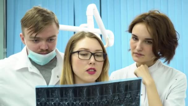 Three young doctors looking at full body x-ray radiographic image, ct scan, mri on hospital clinic cabinet background. Dentists in white lab coats standing and discussing diagnosis.