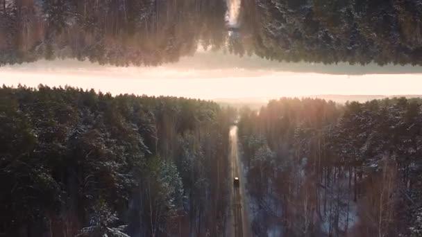 Autó vezetés téli az erdő országút, légifelvételek napnyugtakor ég háttér, tükör horizon hatása. Jármű vezetés mentén az út körül erdő, kezdeti koncepció.