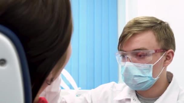 Nahaufnahme für Zahnarzt in Latex-Handschuhe, Maske und Gläser halten dental Lampe näher, der Patient sitzt auf einem Stuhl zu bewegen. Zahnärztliche Beratung in der Klinik